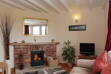 This cosy sitting-room has comfortable sofas and a wood-burner making this cottage a great choice out-of-season,