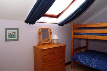 Bedroom 3 has bunk-beds and a sloping ceiling with a Velux window.