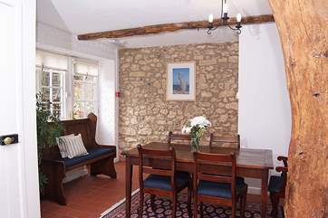 The dining-area has a lovely natural stone wall. The door leads straight out onto the garden.