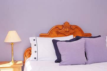 A lovely carved bedhead and stylish colours feature in this room.