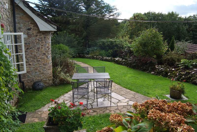 The garden has a sunny terrace and a lovely area of lawn.
