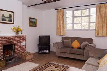 The light and cosy sitting-room with open fire and tasteful furnishings.
