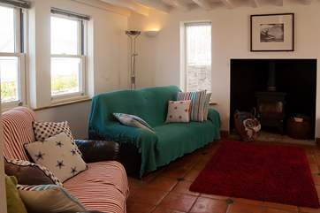 The sitting-room is spacious and cosy all at the same time with a wood-burner to warm your toes on those cooler evenings.