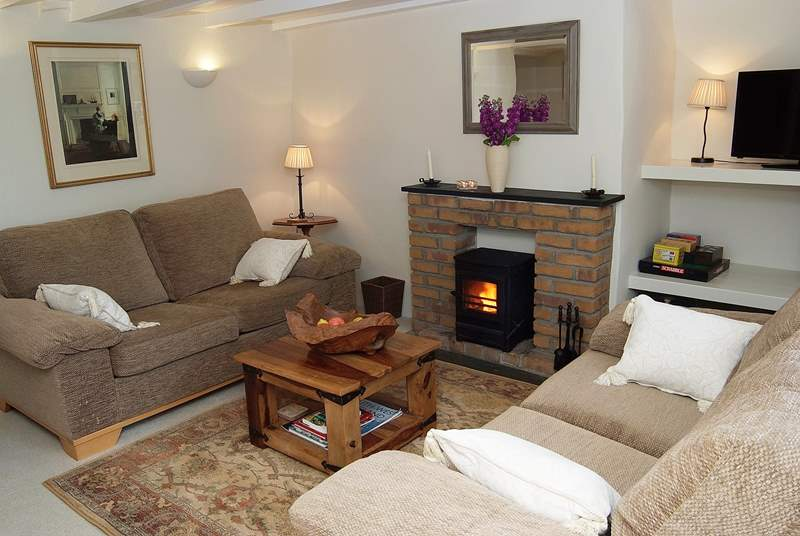 The sitting-room is furnished beautifully with cosy sofas flanking the wood-burner.