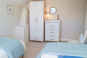 The twin bedroom is fitted with hanging and drawer space.