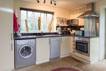 There is a really well equipped kitchen to one side of this bright and cheerful open plan cottage.