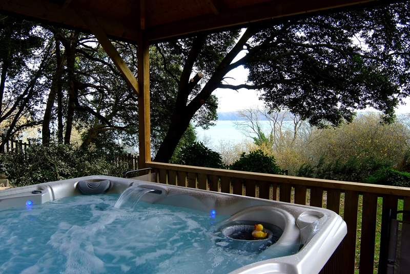 The hot tub looks out to the water.