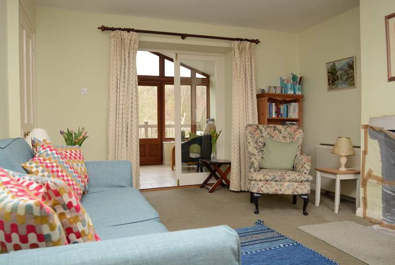 The cosy sitting room with the garden room beyond, beautiful views over the garden and the valley beyond.