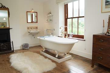The bath in the master bedroom en suite is an old roll-top bath with Victorian hand shower attachment.