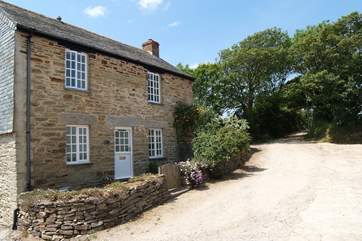 The little front terrace leads round to the private enclosed side garden, The private parking-area is a few yards beyond the cottage, on the left.