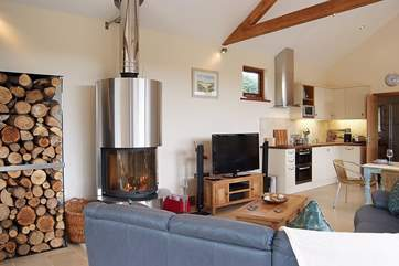 The comfortable sofa surrounds the wood-burner and logs.