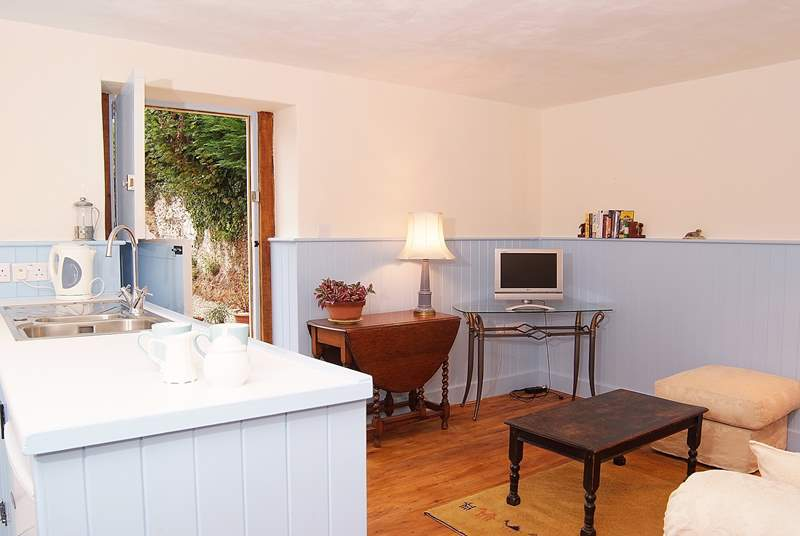 The open plan ground floor is bright and cheerful, with a door to the sitting-out area tucked around the corner.