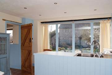 Bright and cheerful colours fill this pretty cottage. This is the kitchen bar with cleverly fitted curtain panels to ensure privacy.