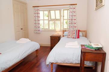 The twin bedroom, Bedroom 3, looks out over the garden and towards the orchard and woodland at the top of the hill.