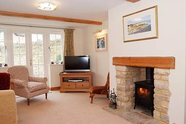 The sitting-room has a wood-burner and French windows to the enclosed garden.