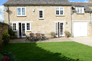 Two sets of French windows lead out onto the patio and enclosed garden.