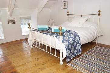 The second floor double bedroom has a beautiful bedstead, crisp white linens and a stunning view out across the harbour.