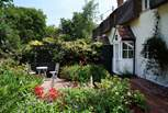 The beautiful cottage garden to the front includes a south-facing seating-area.