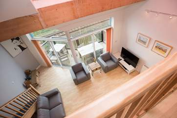 The floor to ceiling doors and windows allow the light to flood into the open plan living-room and mezzanine level above.