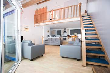 The first floor open plan living area has stairs up to the galleried bedroom.
