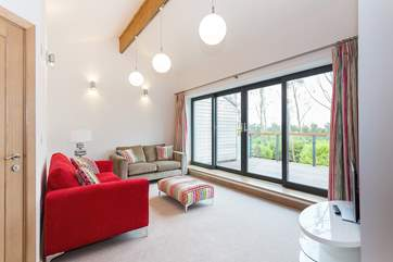 The sitting-room on the first floor has doors out onto a big deck with views over trees and lawns.