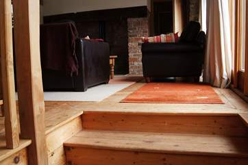 There are wooden stairs  leading from the kitchen to the sitting-room.