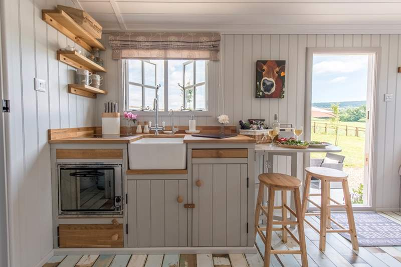 The kitchen window looks out over the patio and farmland beyond. There is a two-ring hob and mini oven and a gas fridge.
