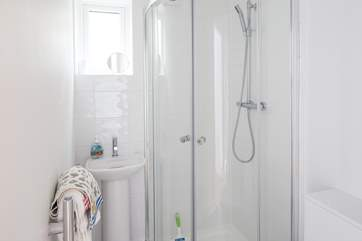 The en suite to the master bedroom is very compact with a drench shower head and petite hand basin.