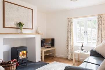 The sitting end of the open plan living room has the sofas around the wood-burner.