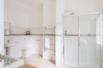 This huge bathroom includes a large shower cubicle.