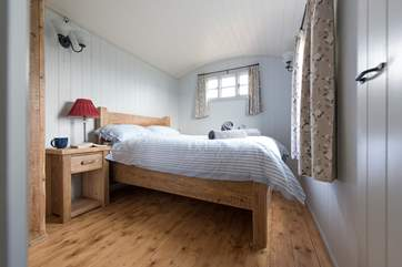 Situated at one side of the hut, pretty bedroom one has a double bed.