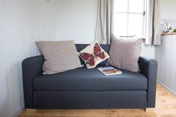 The comfy sofa can also pull out to become a bed, if required.