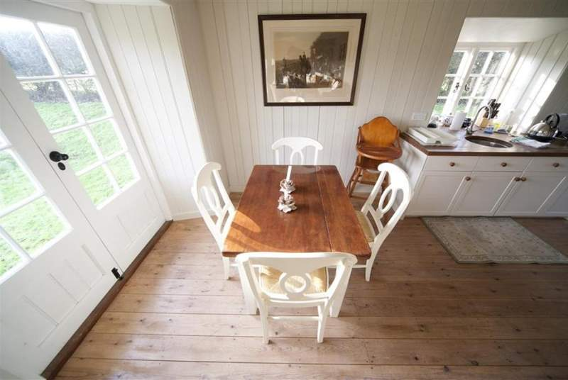 The dining and living area has doors open to the lovely grounds at the rear