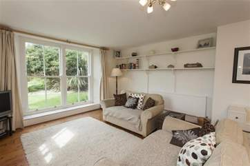 The beautiful living room has big windows looking out to the lovely garden