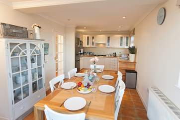 Open plan kitchen/dining-room with doors opening onto the front balcony.