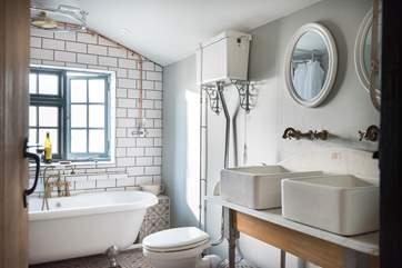 Two sinks, a large shower rose and a shower attachment makes for a very well-equipped bathroom.