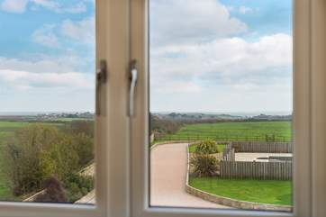 The view from bedroom 3 across the front garden and pool area towards Lizard Point and the sea beyond.