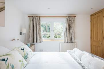 The gorgeous bedroom has a built-in wardrobe and good-size bedside cabinets with plenty of drawer space.