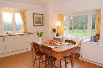 There is a farmhouse kitchen table for breakfast time, with a window seat with amazing views over the garden.