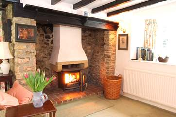 The large living room has a cosy wood burning stove at one end.