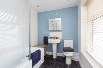 The family bathroom has a bath and a shower and is a bright contemporary room.