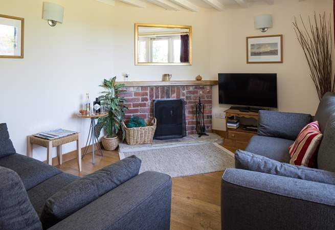 The cosy sitting-room has comfortable sofas and a wood-burner making this cottage a great choice out-of-season.
