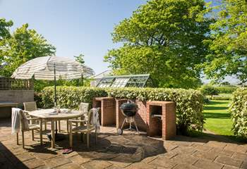 The sunny patio overlooks the large garden.