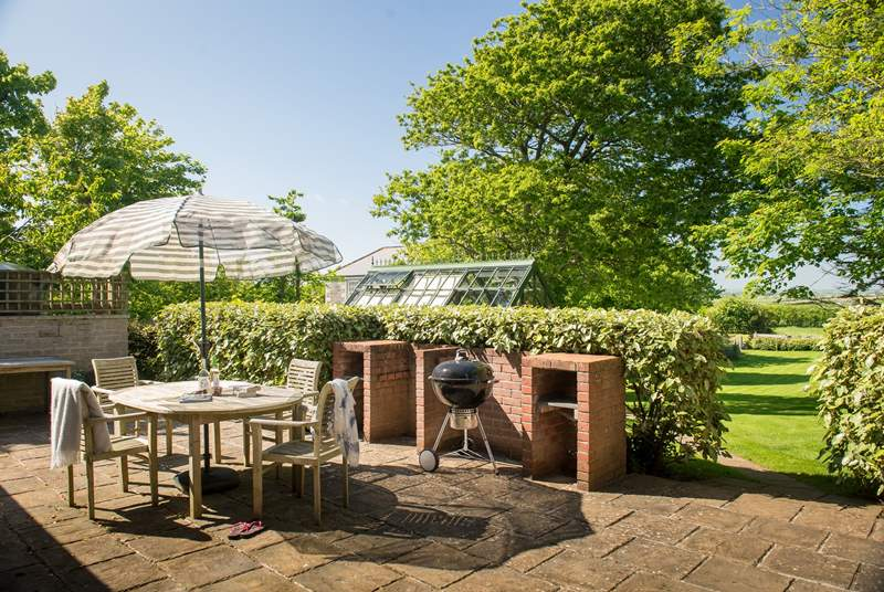 The sunny patio overlooks the large garden.