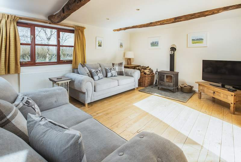 The double aspect sitting-room has views over the garden and the lane and enjoys the joy of a log burner for those cosy nights.