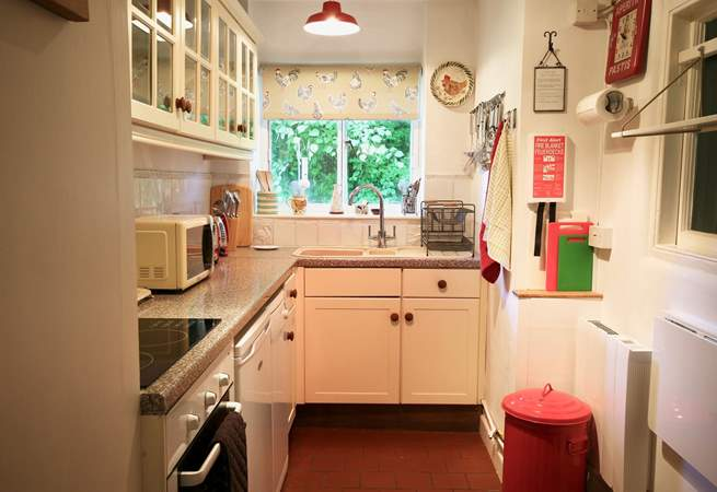 The extremely well equipped kitchen looks out over the side garden and to the field beyond.