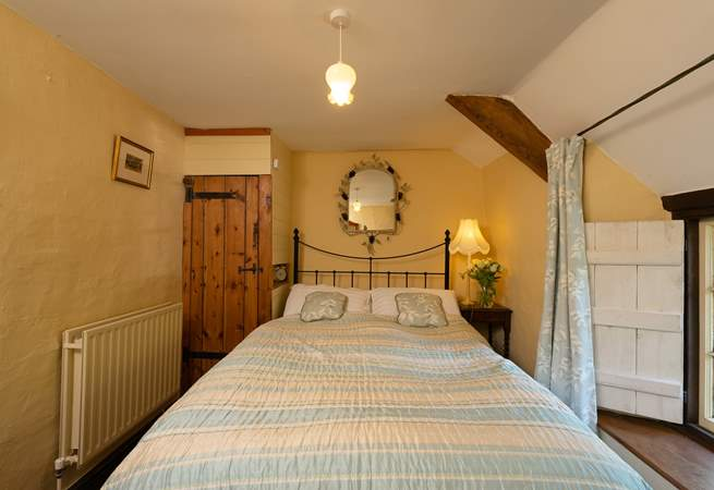The master bedroom with its antique brass bed is on the first floor, at the top of the turning cottage stairs.