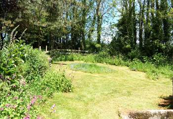 The lawn behind the cottage slopes up towards the surrounding trees.