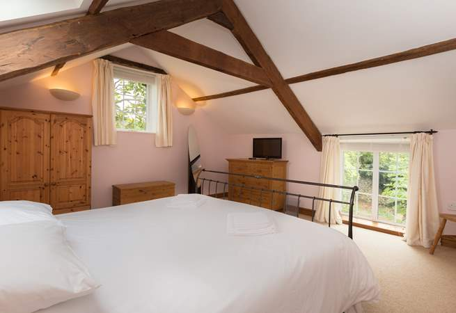 The dual aspect master bedroom has high beamed ceilings and plenty of storage space.