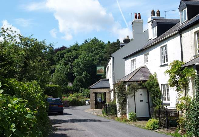The village street with the pub down the road on the right.